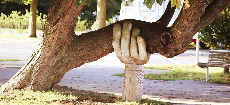 Holzhand stützt schiefen Baum