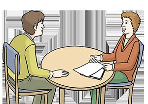 Ein Ratsuchender und ein Berater sitzen an einem Tisch