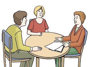 Zwei Personen sitzen an einem Tisch und  werden von einer dritten Person beraten.