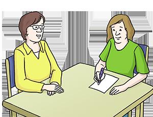 Eine Person hilft einer anderen beim Schreiben