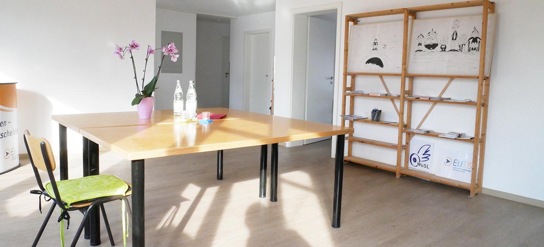 Foto: Großer Besprechungsraum mit Tischen und Regalen, sonnig