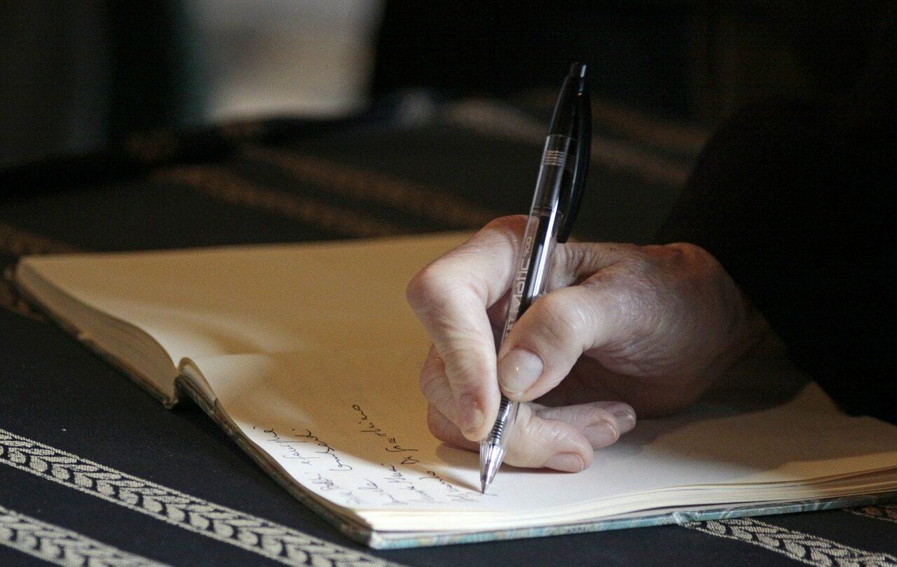 Eine Hand, die einen Stift über einem Dokument hält